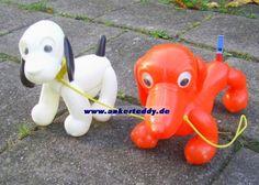 """ankerteddy - PGH Koppelhund / VEB Plast- und Plüschspielwaren Koppelhund 2 Hunde aus Plastik sog. """"Plastespielzeug"""" Entwurf: Ali Kurt Baumgarten PGH Koppelhund/ VEB Koppelhund nach 1959 bis in die 1970er Jahre (?) Plastik, mit Halsband und Leine, Wackelaugen.Der orangefarbene Hund hat eine Pfeife als Schwanz."""