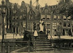 """Amsterdam Jordaan en omgeving  Geïllustreerd weekblad De Prins van 3 juli 1915: """"Een typisch brokje oud-Amsterdam. Op den voorgrond een ouderwetsch houten bruggetje, voerende van de Westerkade naar de Lijnbaansgracht; de oude geveltjes over de brug zijn gelegen nabij de Tuinstraat. Onlangs is in den Gemeenteraad besloten, de houten brug door een nieuwe, meer practische natuurlijk, te vervangen."""""""