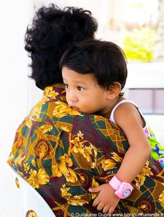 Child waiting for the boat in her grandmother's arms.