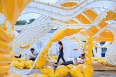 The long, undulating structure glows from within and is filled with dozens of inflatable couches.