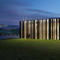 Giant's Causeway Visitors' Centre by Heneghan Peng Architects 愛爾蘭公司赫尼根彭建築圍繞這一遊客服務中心的石窗櫺是模仿火山形成巨人堤道的高聳的玄武岩柱。