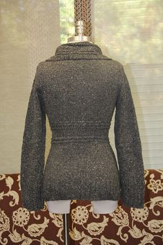 Nonpareil is an everyday cardigan, the kind you will wear all through the winter. It features a wide lapel collar and an accentuated waist with touches of twisted rick-rack like stitches throughout. The central band is knit like a scarf and the tops and bottoms are knit up and out from there, making this an unusually fun knit. (Berroco)