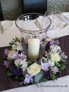 Wedding flowers - glass storm lantern table centre with a ring of flowers & foliage - by Floral Accents