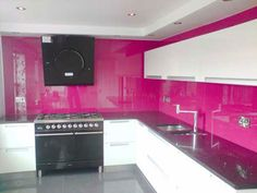 Pantone Magenta glass splashback and glass worktop (in far right of picture). These glass features were supplied by KLG Glass and fitted by our customer.