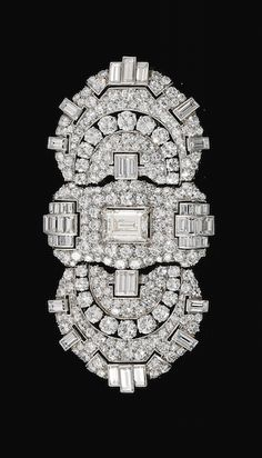 DIAMOND TRIPLE-CLIP BROOCH, BULGARI, 1930S Centring on a step-cut diamond within a plaque pavé-set with circular-cut diamonds, between pierced shield-shaped motifs set with similarly-cut stones and highlighted with baguette diamonds, signed Bulgari, indistinct maker's marks, detachable brooch fitting, may be worn as three separate clips, each signed Bulgari.