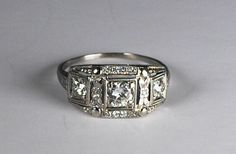 This versatile ring in 18kt white gold from the Art Deco era is perfect as a combination engagement ring/wedding band, a wide wedding band to match your vintage engagement ring, or as a right-hand ring. This ring is big on design and bling, but sits low on the hand for comfort. Three European cut diamonds are set across the top in squared bead settings ornamented with artful filigree work, decorative embossing and fine millegrain details. The two side stones weigh approximately .20 carat...