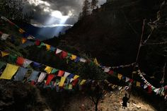 A Bhutanese man walks past prayer flags at Taktsang Monastery, also known as the Tiger's Nest, outside Paro, Bhutan, on April 30, 2010.