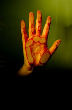 Woman's bloody hand against a glass window