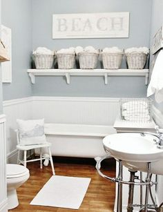 Beach huse with a vintage bath with claw foot tub, baskets for towel storage, beaded board walls.