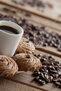 cup of hot coffee and delicious chocolate cookies - Cup of hot coffee and delicious chocolate cookies with lots of coffee beans