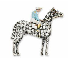 A VICTORIAN ENAMEL AND DIAMOND HORSE AND JOCKEY BROOCH The horse realistically modelled at rest, pavé-set with circular-cut diamonds and an enamel saddle and brow-band, the jockey with painted enamel racing colours, mounted in silver and gold, circa 1890, 3.6cm wide