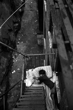 This photo shows a child sleeping on a fire escape in the Bronx. This child is homeless and it is just so sad that this child doesn't have a roof over their heads to be able to sleep comfortable at night. I do not believe any child should live this way.