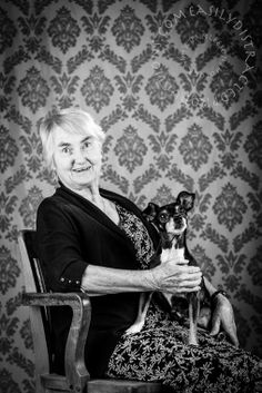 Mother with Maya, a Toy Fox Terrier mixed with Jack Russell. Portrait. Vintage back drop. Black and white. In old wood chair.