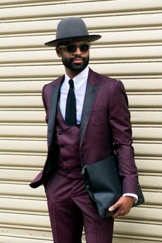 A showgoer in a burgundy suit accessorized with a clutch and wide-brimmed hat. (Photo: Marcy Swingle for The New York Times)