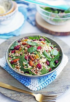 Colourful Farro and Spinach Salad with Dried Fruit and Nuts in a wooden bowl with a fork to its side.