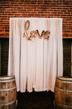 Pretty ceremony backdrop with shear white curtains, wine barrels, and metallic gold LOVE balloon | Image by Courtney Smith Photography