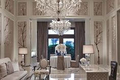 A table with formal place settings and a floral centerpiece sits underneath a chandelier and in front of glass doors