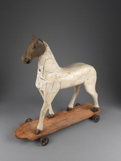 Folk Art - Collection - Robert Young Antiques Sculptural Folk Art Toy Horse with Rare Cast Iron Head, Raised on a Platform Base and Original Wheels , Carved Block Constructed Painted Wood and Cast Iron, Continental, c.1870