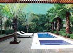 Maciços desordenados de bananeiras e alpínias revelam a tropicalidade do jardim. O deque de itaúba abraça a piscina e se desdobra em um banco. Projeto do paisagista Alex Hanazaki.