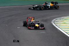 Sebastian Vettel of Germany and Red Bull Racing drives past debris on the track during the Brazilian Formula One Grand Prix