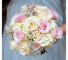 Hand tied bouquet of cream and pale pink roses, cream hydrangea and dots of babies breath.