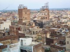 Gujrat rooftops, Punjab, Pakistan.The huge structures on top of the two of the taller houses are cages for keeping pigeons, a common sight in inner parts of cities like Lahore, Gujranawala & Faisalabad among others.