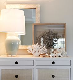 A 6-Drawer dresser in white and grasscloth finish holds an assortment of seashells, sea glass, and corals. A mirror with a herringbone pattern of inlaid bone reflects the light from a sea foam green acrylic based lamp with a linen shade. by Chango & Co.
