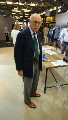 Luciano Barbera in tan monkstrap shoes, mid-gray flannel trousers, striped shirt, and foulard necktie.