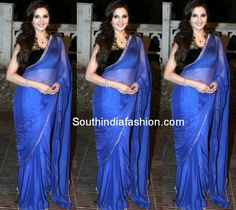Actress Monica Bedi in plain royal blue pure chiffon saree with gold zari border, paired up with black velvet embellished high neck blouse.
