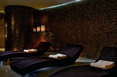 Three lounge chairs with rolled towels on top in a dimly-lit room with walls that look like twinkling stars