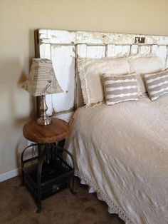 Home made head board! just use an old rustic looking door, clean, screw two 2 or 3 inch pieces of wood on the back to support the door at the height you prefer!