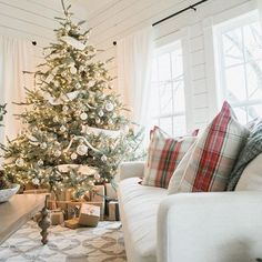 plaid christmas pillows and a white and gold christmas tree
