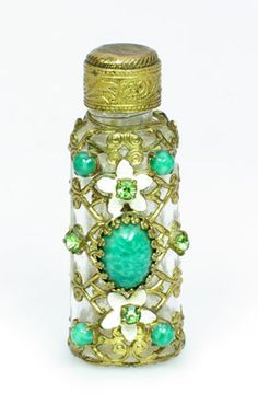 An intricately decorated vintage glass perfume bottle with green stones.  graysantiques.com