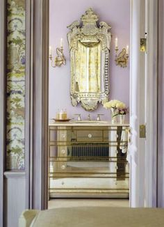 A gilt mirror, mirrored console, and lavender walls create  an ambience both sophisticated and soothing.