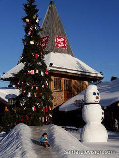 Der Schneemann und kleine glückliche Besucher im Weihnachtsmanndorf in Rovaniemi (Finnland)