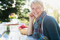 Pretty mid-adult woman smiling while sitting at picnic table.