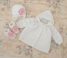 Wool baby sweater, white hat and socks, baby girl baptism outfit, winter baby clothes  Nice Knitted set: jacket with a hood, hat and booties for a babygirl. Fastens with buttons. Decorated knit flowers. Booties are fastened to the shoelaces and fall from the babies legs. Handcrafted, made of wool yarn. Warm, with love for your baby! Size 3-6 months: Length 11,8 inches (30 cm.), Width 9,45 inches (24 cm.) in the chest, sleeve 9,45 inches (24 cm.) booties on foot 4 inches (10 cm.) hat on head…