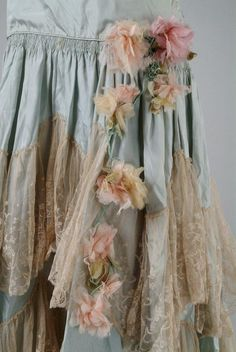 Peggy Hoyt Date Made:1929 Description:Light blue taffeta party dress trimmed with off-white lace. Dress has a skirt with two tiers of off white lace and a bib collar of lace. Pastel colored flowers accent the skirt. Detail