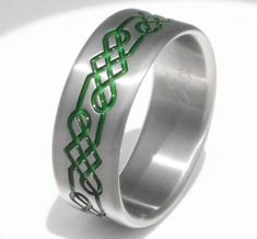A bold shield knot wraps this Titanium Celtic ring with strong style. The intricate design is hand carved into a flat profile titanium band, shown here in 8mm width with emerald-colored grooves and handcrafted here in the USA, the perfect traditional wedding band or promise ring. Wear a ring with enduring appeal that matches your own resilient spirit. #celticweddingringsstyle