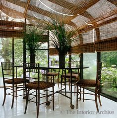 The glass ceiling and walls of the conservatory are covered with long bamboo blinds - Photographer: Mark Luscombe-Whyte  Designer/Stylist: Muriel Brandolini