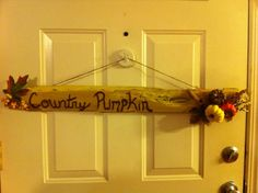 A fall sign made from a wood plank from a wood pallet. Painted and sanded down. Wrote fall message and hot glued the fall foliage to the plank, then attached the cord to back with staple gun.