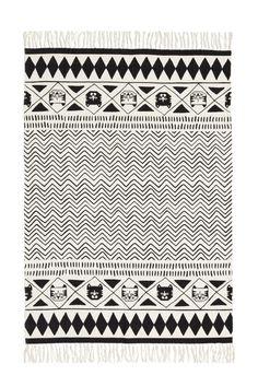 Nyomott mintás, négyszögletű pamutszövet szőnyeg rojtos rövid oldalakkal.