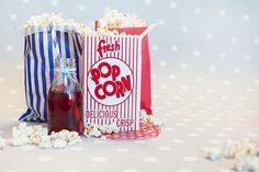 Decoración de fiestas. Bolsas de papel y cajita de cartón Popcorn. Botellita de cristal y pajita de rayas azules y rojas. Blonda roja lunares blancos.