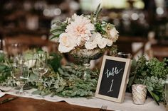 Lots of greenery, chalkboard table number, elegant centerpiece | Image by Jordan Voth