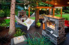 Gorgeous outdoor living area complete with fireplace and hammock [Design: Paradise Restored Landscaping & Exterior Design]