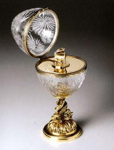 Faberge crystal pian egg.Clear crystal egg mounted on a 24k gold-plated bronze stand. When opened the surprise revealed is a 24k gold-plated sterling silver piano. Height 12""