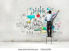 Back view of businessman drawing sketch on wall - stock photo