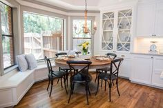 Just off the kitchen is this breakfast nook in a bay window setting with a country table and built-in bench seating.