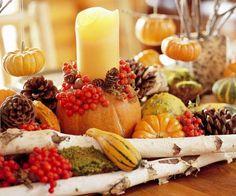 arrangement d'automne original - chandelle blanche, mini citrouilles en jaune et orange, baies rouges et pommes de pin