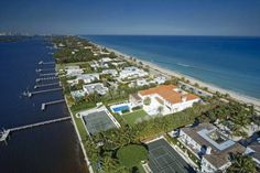 $99 Million - Located between Lake Worth Lagoon and the Atlantic Ocean, this Palm Beach estate is prime waterfront real estate. The property spans 1.86 acres and includes a 200-foot dock, clay tennis courts and a 44-foot glass-tiled pool. A beautiful Mediterranean, the house has 7 bedrooms, 14 bathrooms, a 2-story living room, commercial pizza kitchen and large covered patio. A staircase leads you straight from the house to the beach.